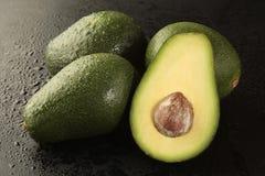 Gruppo di avocado con la metà su priorità bassa nera fotografia stock libera da diritti