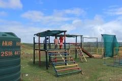 Gruppo di bambini africani che giocano all'aperto in un campo da giuoco, Swaziland, Africa del Sud Fotografie Stock