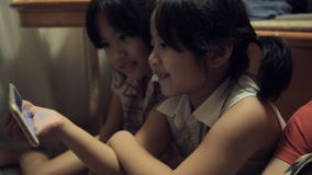 Gruppo di bambini asiatici che giocano con un touchpad a casa video d archivio
