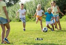 Gruppo di bambini attivi che giocano a calcio insieme sul prato inglese verde dentro Fotografia Stock Libera da Diritti