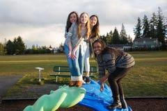 Gruppo di bambini attivi che giocano fuori al campo da giuoco della scuola Fotografie Stock Libere da Diritti