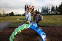 Gruppo di bambini attivi che giocano fuori al campo da giuoco della scuola Immagine Stock