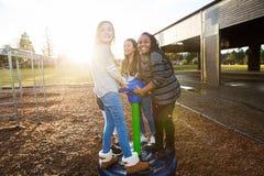 Gruppo di bambini attivi che giocano fuori al campo da giuoco della scuola Immagini Stock
