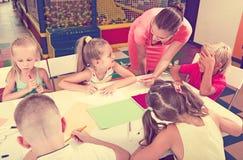 Gruppo di bambini che attingono lezione con aiuto dell'insegnante Fotografie Stock