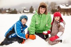Gruppo di bambini che costruiscono pupazzo di neve fotografie stock libere da diritti