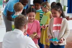 Gruppo di bambini che effettuano esperimento nella classe di scienza immagini stock libere da diritti