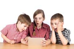 Gruppo di bambini che giocano gioco emozionante sulla compressa isolata su bianco fotografie stock libere da diritti