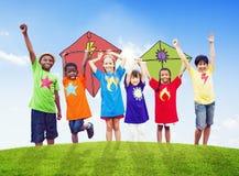 Gruppo di bambini che giocano gli aquiloni all'aperto Immagini Stock Libere da Diritti