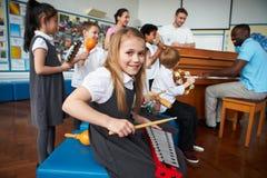 Gruppo di bambini che giocano insieme nell'orchestra della scuola immagini stock libere da diritti