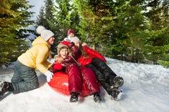 Gruppo di bambini che guidano giù la collina sulla ghiaccio-barca rossa Fotografia Stock
