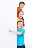 Gruppo di bambini che indicano sull'insegna bianca Immagini Stock