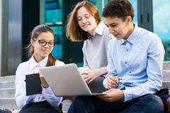 Gruppo di bambini che per mezzo del computer portatile dall'edificio scolastico Immagine Stock