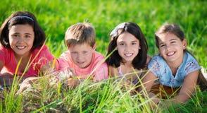 Gruppo di bambini che riposano nel campo Fotografie Stock