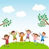 Gruppo di bambini che saltano sulla collina dell'erba con cielo blu Fotografia Stock