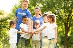 Gruppo di bambini che si prendono per mano con i volontari fotografia stock
