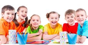 Gruppo di bambini che si siedono ad una tavola Immagini Stock Libere da Diritti