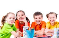 Gruppo di bambini che si siedono ad una tavola Fotografia Stock