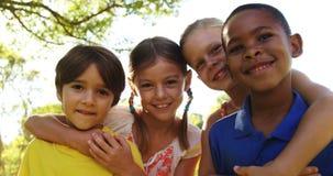 Gruppo di bambini che stanno insieme alle armi intorno archivi video