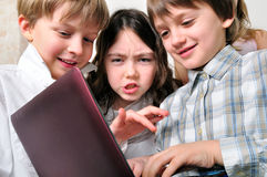 Gruppo di bambini che studiano al computer portatile fotografia stock