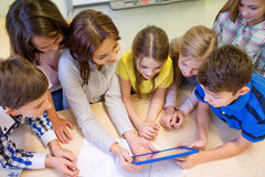 Gruppo di bambini con il pc della compressa e dell'insegnante alla scuola Fotografie Stock