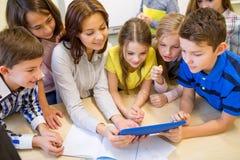 Gruppo di bambini con il pc della compressa e dell'insegnante alla scuola Immagini Stock Libere da Diritti