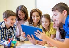 Gruppo di bambini con il pc della compressa e dell'insegnante alla scuola Immagine Stock