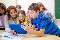 Gruppo di bambini con il pc della compressa e dell'insegnante alla scuola Immagini Stock