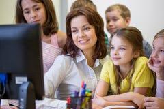 Gruppo di bambini con l'insegnante ed il computer alla scuola Immagine Stock