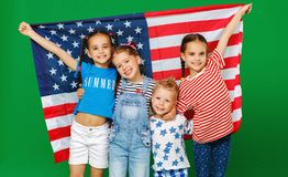 Gruppo di bambini con la bandiera degli Stati Uniti d'America U.S.A. su fondo verde fotografia stock libera da diritti