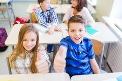 Gruppo di bambini della scuola che mostrano i pollici su Fotografie Stock