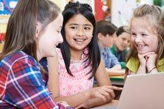 Gruppo di bambini della scuola elementare che lavorano insieme in computer Immagini Stock Libere da Diritti