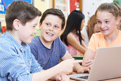 Gruppo di bambini della scuola elementare che lavorano insieme in computer Immagini Stock