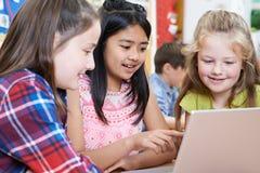 Gruppo di bambini della scuola elementare che lavorano insieme in computer Fotografie Stock Libere da Diritti