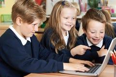 Gruppo di bambini della scuola elementare che lavorano insieme in computer Immagine Stock Libera da Diritti