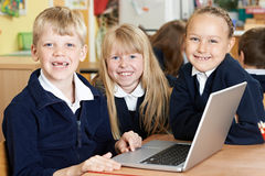 Gruppo di bambini della scuola elementare che lavorano insieme in computer Fotografia Stock