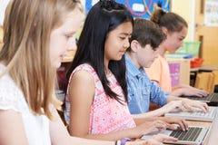 Gruppo di bambini della scuola elementare nella classe del computer Immagini Stock Libere da Diritti