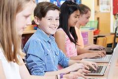 Gruppo di bambini della scuola elementare nella classe del computer Immagini Stock