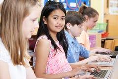Gruppo di bambini della scuola elementare nella classe del computer Immagine Stock