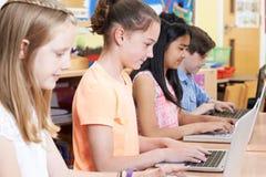 Gruppo di bambini della scuola elementare nella classe del computer Fotografia Stock