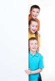 Gruppo di bambini dietro l'insegna bianca. fotografie stock