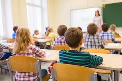 Gruppo di bambini e di insegnante della scuola in aula fotografia stock libera da diritti