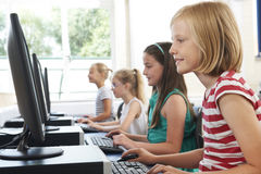 Gruppo di bambini femminili della scuola elementare nella classe del computer Immagine Stock Libera da Diritti