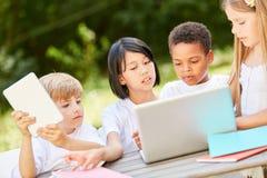 Gruppo di bambini nel lavoro di squadra al computer portatile fotografie stock