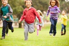 Gruppo di bambini piccoli che corrono verso la macchina fotografica in parco Immagine Stock