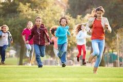 Gruppo di bambini piccoli che corrono verso la macchina fotografica in parco Fotografia Stock
