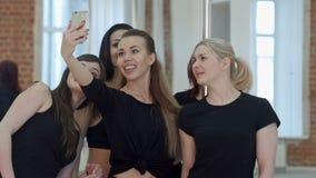 Gruppo di belle giovani donne che prendono un selfie durante una pausa su una classe di forma fisica del palo stock footage