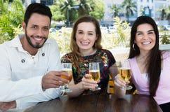 Gruppo di birra bevente caucasica e latina della donna e dell'uomo in una barra fotografia stock libera da diritti
