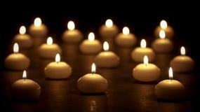 Gruppo di candele burning ad una priorità bassa nera Fotografie Stock