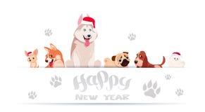 Gruppo di cani svegli che si siedono sul fondo bianco con le stampe del piede che indossano l'insegna 2018 di anno di Santa Hat A Fotografie Stock