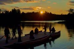 Gruppo di canoers, preparante fare canoa, tramonto fotografia stock libera da diritti
